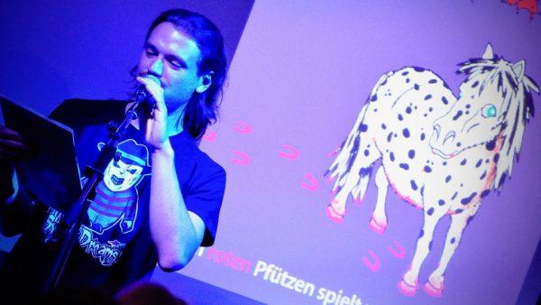 Marien Loha liest an Halloween mit einem Dalmatinerpony im Hintergrund.